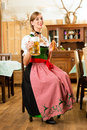 Young woman in traditional bavarian tracht in restaurant or pub with beer and steins and pretzel Royalty Free Stock Photo