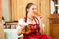 Young woman in traditional bavarian tracht in restaurant or pub with beer and steins and pretzel Royalty Free Stock Photography
