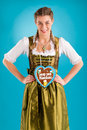 Young woman in traditional clothes dirndl or tracht bavarian with a gingerbread souvenir heart Royalty Free Stock Images