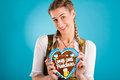 Young woman in traditional clothes dirndl or tracht bavarian with a gingerbread souvenir heart Stock Images