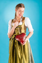 Young woman in traditional clothes dirndl or tracht bavarian with a valentines heart Royalty Free Stock Images