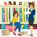 Young woman trying on different shoes with help of shoe store assistant attractive Royalty Free Stock Photos
