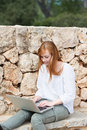 Young woman typing on her laptop keyboard sitting an old stone wall and enjoying the sunshine Royalty Free Stock Photo