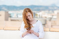 Young woman typing an sms beautiful redhead standing on a rooftop terrace overlooking a coastal town on her mobile Royalty Free Stock Image