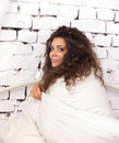 Young woman under duvet beautiful with long dishevelled curls sitting on white bricky wall background Royalty Free Stock Images