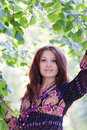 Young woman under green tree in spring park Royalty Free Stock Photo