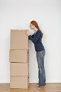 Young woman unpacking boxes side view of a opening the top box of a stack of moving and searching for an item Stock Images