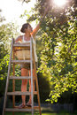 Young woman up on a ladder Royalty Free Stock Photography