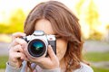 Young woman uses digital slr photocamera Royalty Free Stock Photography