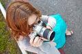 Young woman uses digital slr photocamera Royalty Free Stock Photography