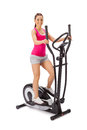 Young woman uses elliptical cross trainer Stock Photos