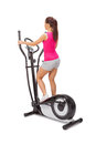 Young woman uses elliptical cross trainer Royalty Free Stock Photography