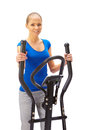 Young woman uses elliptical cross trainer Royalty Free Stock Image