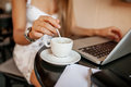 Young woman uses laptop in cafe blond drinking coffee Royalty Free Stock Photo