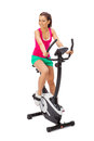 Young woman uses stationary bicycle trainer Royalty Free Stock Photo