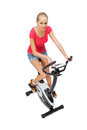 Young woman uses stationary bicycle trainer Royalty Free Stock Photos