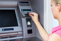 Young woman using a atm put credit card into Royalty Free Stock Photos