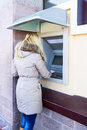 Young woman using bank atm cash machine street Stock Photo