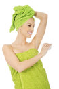 Young woman using deodorant wrapped in towel Stock Images