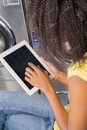 Young woman using digital tablet in laundry closeup of Stock Photography