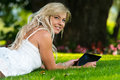 Young woman using a digital tablet in the park lying on grass with Royalty Free Stock Image