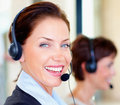 Young woman using headset with people in a row Stock Images