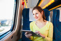 Young woman using her tablet computer while traveling by train Royalty Free Stock Images