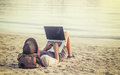 Young woman using laptop computer on a beach. Freelance work con Royalty Free Stock Photo