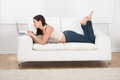 Young woman using laptop while lying on sofa side view portrait of at home Royalty Free Stock Images