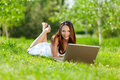 Young woman using laptop in park Stock Image