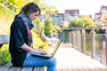 Young woman using laptop at a riverbank. Royalty Free Stock Photo