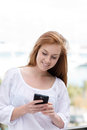 Young woman using a smart phone standing outdoors reading text message with smile Stock Photography