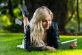 Young woman using tablet notebook lying on grass with digital Royalty Free Stock Photos