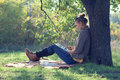Young woman using tablet pc hipster style during a rest under the tree Stock Image