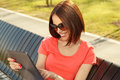 Young woman using tablet pc sits in a park on a wooden bench and selective focus on face Royalty Free Stock Photography