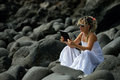 Young woman using tablet on rocky beach in summer black sunny day Stock Photo