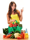 Young woman with variety of grocery products in shopping bag on white Stock Images