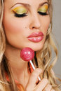 Young woman with vibrant makeup holding a lollipop Stock Image