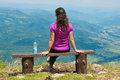 Young woman at the viewpoint pretty brunette girl sitting on bench oslusa on tara mountain Royalty Free Stock Image