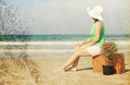 Young woman with vintage suitcase om the beach photo in old color image style Royalty Free Stock Photos