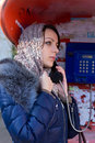 Young woman waiting patiently for a call beautiful on public telephone to be connected staring into the distance close up side Stock Photography