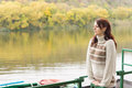 Young woman waiting at a tranquil river beautiful standing on deck above moored rowboat enjoying the peace of the autumn Stock Photography