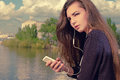 Young woman waiting your call. Dressing in a black wear,  a young caucasian lady is standing by river, holding a mobile Royalty Free Stock Photo