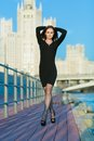 Young woman walking along the waterfront smiling in a black dress Royalty Free Stock Photos