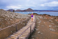 Young woman walking on a boardwalk on Bartolome island, Galapagos National Park, Ecuador. Royalty Free Stock Photo