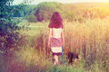 Young woman walking with dog on the wheat field Stock Photography