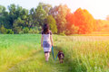 Young woman walking with dog on the wheat field Royalty Free Stock Image