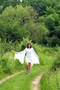 Young woman walking happy caucasian brunette in white dress on green rural road Stock Image