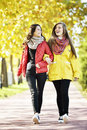 Young woman walking happy two girl in autumn park friends Royalty Free Stock Images
