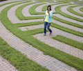 Young Woman Walking Through Maze with Cellphone Royalty Free Stock Photo